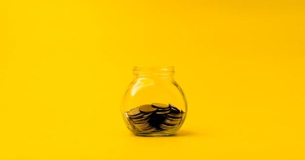 Münze in glasflasche, um geld zu sparen finanzielle geschäftsinvestitionsideen kopieren sie platz für ihren text. auf gelbem grund