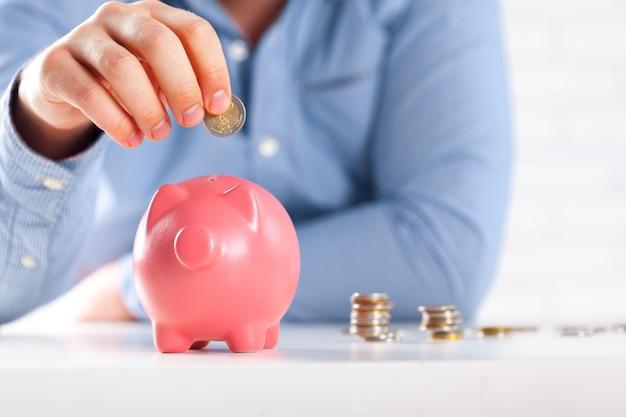 Münze ins sparschwein stecken