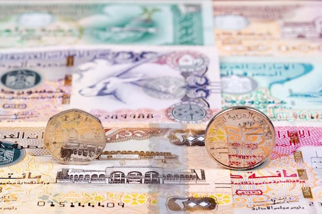 Münzen aus den vereinigten arabischen emiraten vor dem hintergrund der banknoten