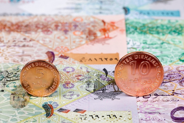 Münzen aus katar vor dem hintergrund der banknoten
