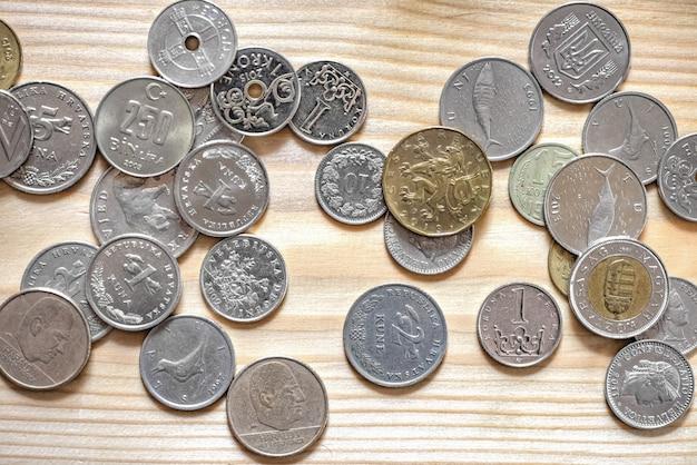 Münzen aus verschiedenen ländern liegen auf einer holztischfläche