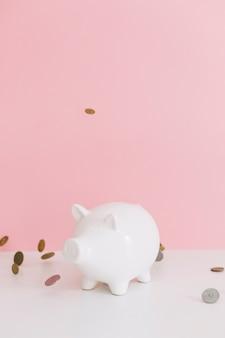 Münzen, die über das weiße piggybank über dem schreibtisch fallen