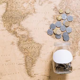 Münzen, die vom glas über der weltkarte verschütten
