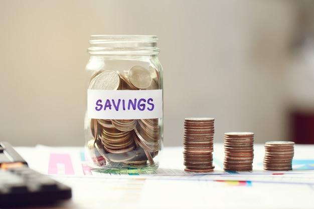 Münzen im glas auf business-grafik. konzept für wachstum und geld sparen