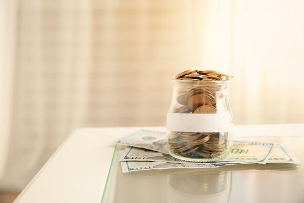 Münzen im glas und geldscheine auf dem tisch