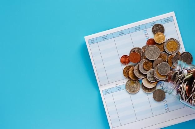 Münzen im glasgefäß und draußen, thailändisches währungsgeld auf buch der planung und der speicherung