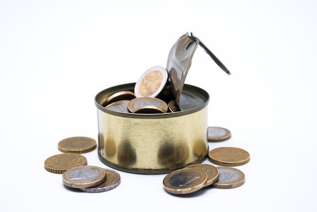 Münzen im offenen zinn auf weißem hintergrund
