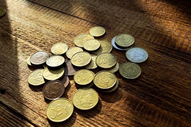Münzen im sonnenstrahl auf dem hölzernen hintergrund