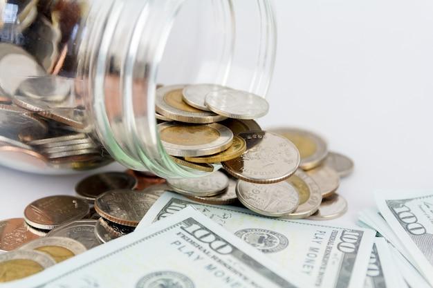 Münzen in der flasche und verspotten bargeld mit weißem hintergrund.