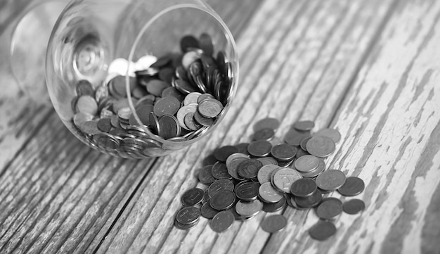 Münzen in einem glas auf dem boden. angesammelte münzen auf dem boden. tascheneinsparungen in haufen.