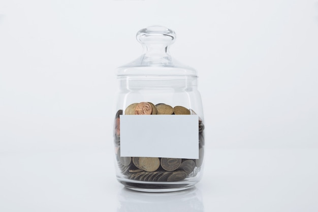 Münzen in einer glasbank mit platz für text in einem weißen raum. einzahlungskonzept