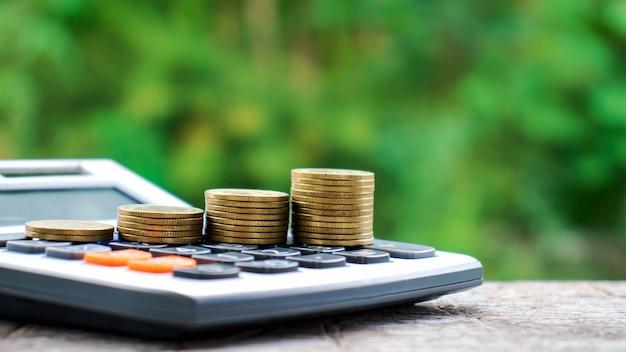 Münzen oder geld auf taschenrechnern, finanzbuchhaltungskonzepten und geld sparen