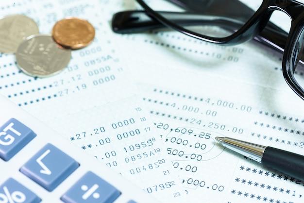 Münzen, plastikgläser, taschenrechner, stift, buchbank auf dem tisch