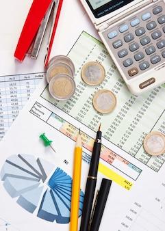 Münzen und das arbeitspapier mit einem diagramm