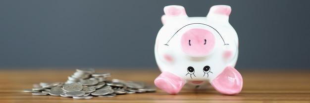 Münzen und ein umgedrehtes sparschwein liegen auf dem tisch konkurs von unternehmen und privatpersonen