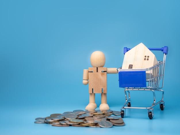 Münzen und holzpuppen, die neben dem einkaufswagen stehen mit einem modellholzhaus auf blau