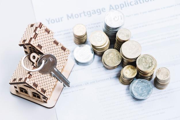 Münzen und schlüssel auf dem blatt der hypothekenantrag