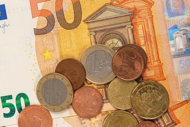 Münzen vor dem hintergrund von fünfzig euro-banknoten, nahaufnahme