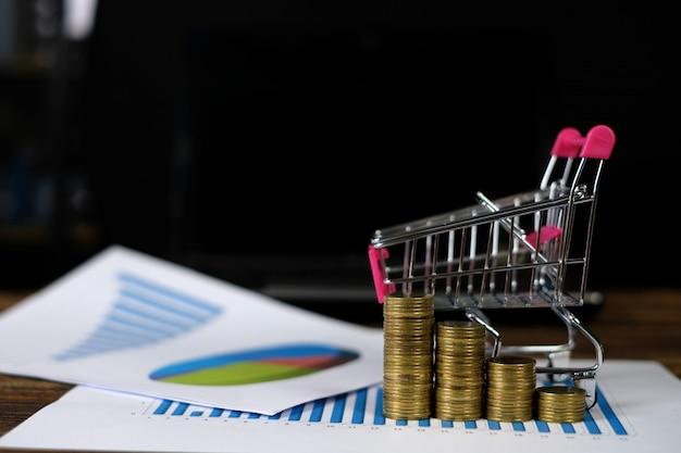 Münzenstapel mit laufkatze und notizbuch und finanzdiagramm