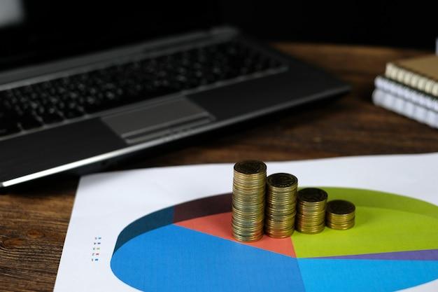 Münzenstapel mit notizbuch und finanzdiagramm