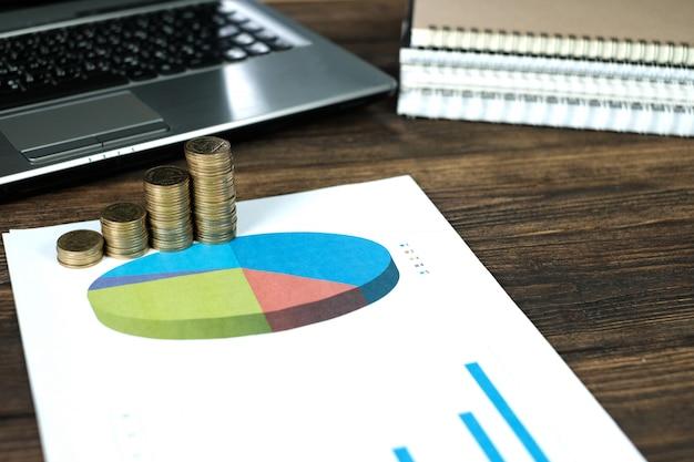 Münzenstapel mit notizbuchlaptop-computer und finanzdiagramm