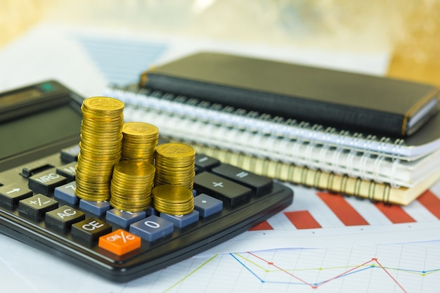 Münzenstapel und finanzielles millimeterpapierblatt mit taschenrechner auf arbeitstisch, unternehmensplanungsvision und finanzanalysekonzept.