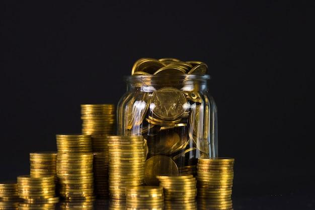 Münzenstapel und goldmünzgeld im glasgefäß auf dunklem hintergrund