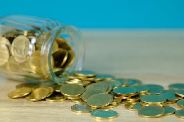 Münzenstapel und goldmünzgeld im glasgefäß