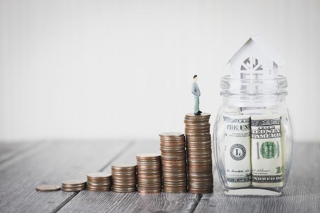 Münzgeldstapel verstärken weißes haus auf dollarscheinen, immobilieninvestition, haushypothek