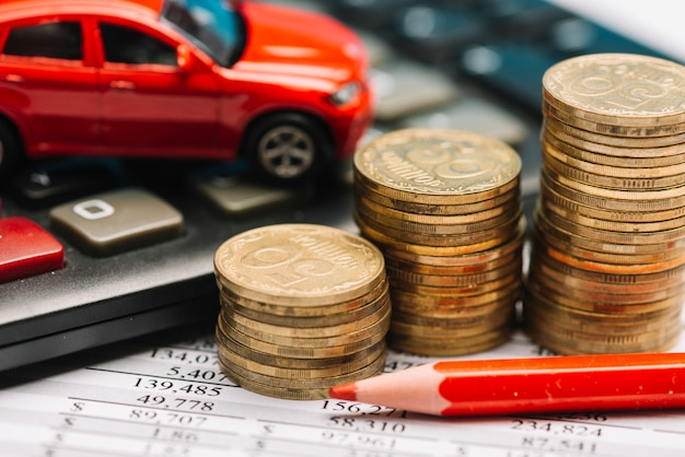 Münzstapel; taschenrechner; spielzeugauto auf finanzbericht mit rotem farbigem bleistift