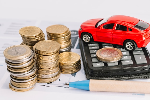 Münzstapel; taschenrechner; spielzeugauto und stift auf vorlage