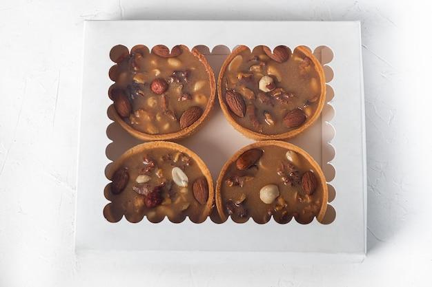 Mürbeteigkuchen mit nüssen und karamell auf hellem hintergrund. hauslieferung.
