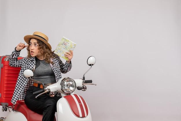 Mürrische junge frau auf moped mit karte auf grau