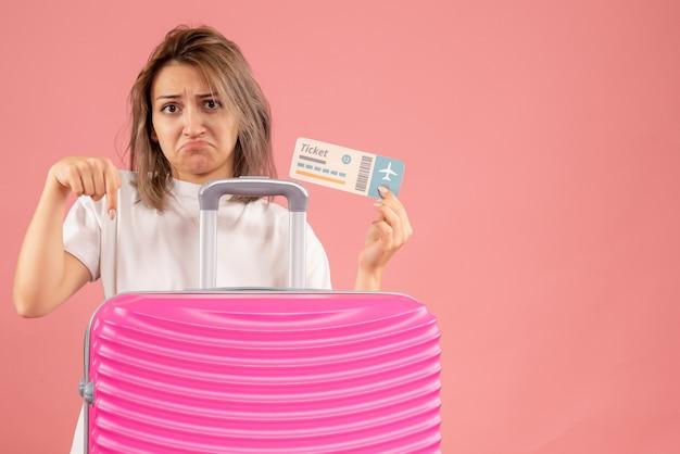 Mürrische junge frau mit ticket zeigt auf koffer