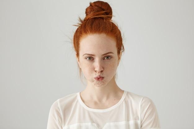 Mürrische störrische junge ingwerfrau mit haarknoten, die wangen bläst und schmollt, während sie sich wütend auf freunde fühlt, die vergessen haben, sie zum feiern einzuladen. menschliche emotionen, gefühle, haltung, reaktion