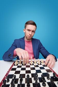 Mürrischer junger mann, der dich ansieht, während er am schachbrett sitzt und isoliert alleine spielt