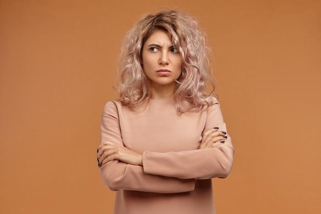 Mürrisches hartnäckiges hipster-mädchen mit voluminösem haar, das respektlosigkeit und gleichgültigkeit ausdrückt, nicht mit ihnen spricht und mit unzufriedenem gesichtsausdruck wegschaut