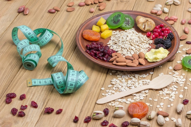 Müsli ausgewogenes frühstück. früchte, beerensamen, nüsse, vegetarisches eiweiß. plan für eine gesunde ernährung. maßband auf holzoberfläche