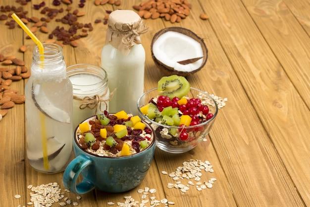 Müsli ausgewogenes proteinfrühstück. früchte, beerensamen, nüsse. kokosgetränk und joghurt. gesunde ernährung vegetarisches essen.