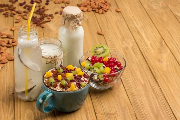 Müsli ausgewogenes proteinfrühstück. früchte, beerensamen, nüsse. kokosgetränk und joghurt.