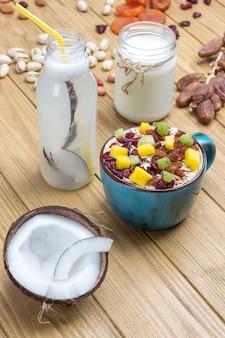 Müsli ausgewogenes proteinfrühstück. früchte, beerensamen, nüsse, kokosnuss. kokosgetränk und joghurt. gesunde ernährung vegetarisches essen. draufsicht holzoberfläche.