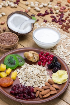 Müsli ausgewogenes proteinfrühstück. früchte, beerensamen, nüsse, kokosnuss. kokosjoghurt. gesunde ernährung vegetarisches essen. draufsicht holzoberfläche.