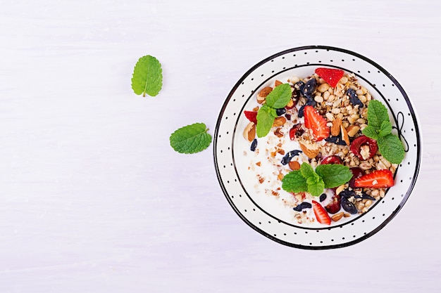 Müsli, erdbeeren, kirsche, geißblattbeere, nüsse und joghurt in einer schüssel