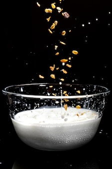 Müsli fallen in eine glasschüssel milch auf einem dunklen hintergrund