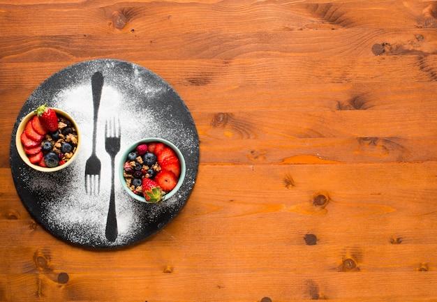 Müsli. frühstück mit müsli und frischen früchten in schalen auf rustikalem holzuntergrund,