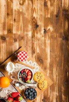 Müsli. frühstücken sie mit müsli und frischen früchten in den schüsseln auf einem rustikalen hölzernen hintergrund
