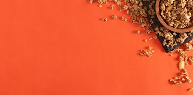 Müsli-getreide und mandeln auf schiefertablett und korkschale auf orangem hintergrund. flach liegen. platz kopieren.