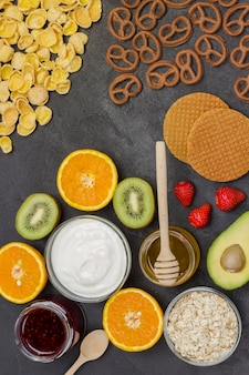 Müsli, kekssaft, fruchtmarmeladenplätzchen, erdbeeren, kiwi, honig, orangensaft.