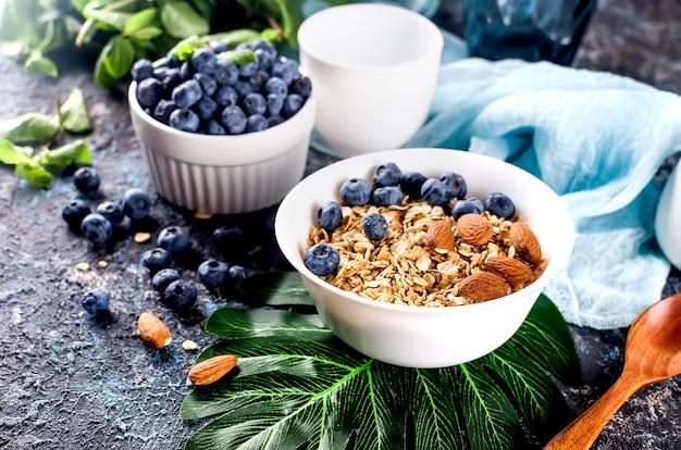Müsli mit blaubeeren in weißem teller und einer tasse tee zum frühstück, hausgemachtes gebackenes müsli mit nüssen und honig für wenig süße.