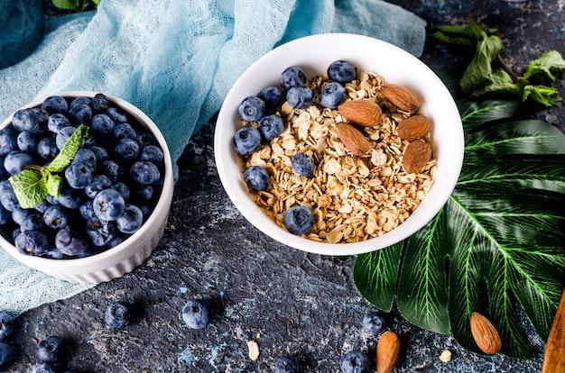 Müsli mit blaubeeren in weißem teller und tasse tee zum frühstück,
